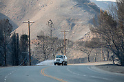 Vehicle spraying water along Kanan Dume Road. The Woolsey wildfire started on November 8, 2018 and has burned over 98,000 acres of land, destroyed an estimated 1,100 structures and killed 3 people in Los Angeles and Ventura counties and the especially hard hit area of Malibu. California, USA