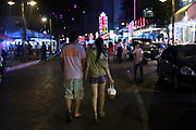 A couple walks down Beer Street carrying a plastic bag of freshly brewed Tsingtao beer in downtown Qingdao, Shandong Province, China on 23 August 2012. Qingdao is recognized as one of the most livable cities in China.