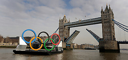 © Licensed to London News Pictures. 28/02/2012, London, UK. Tower Bridge is raised to allow giant Olympic rings measuring 11 metres high by 25 metres wide are floated down the River Thames on a barge, marking 150 days to go to the start of the London 2012 Olympic and Paralympic Games. Photo credit : Stephen Simpson/LNP
