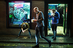 "© Licensed to London News Pictures . 23/12/2017. Manchester, UK. A man sits in the window of a takeaway on Bootle Street , leaning over a pool of vomit between his feet . Revellers out in Manchester City Centre overnight during "" Mad Friday "" , named for being one of the busiest nights of the year for the emergency services in the UK . Photo credit: Joel Goodman/LNP"