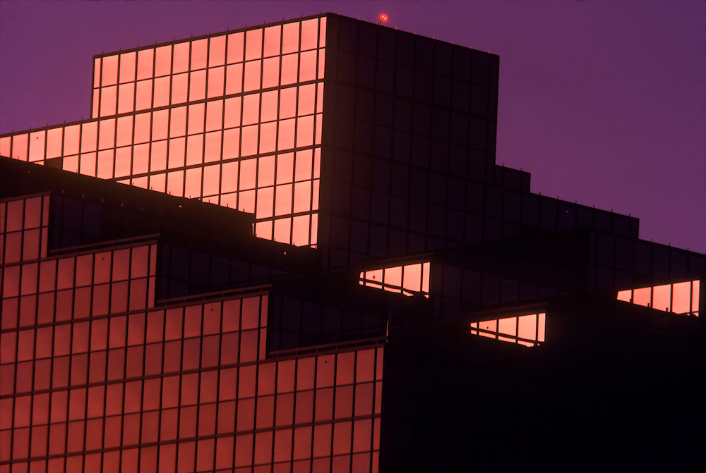 Office Building shot from helicopter, Greenspoint, Houston, Texas. Pink reflection of sunlight on glass of building with a purple sky in the background. Built in the bauhaus, or modernistic form of architecture.
