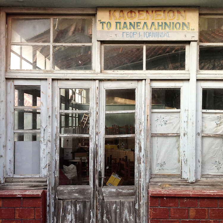 An abandoned coffeehouse in th village of Sykamia in Lesbos island. The sign reads Panhellenic.