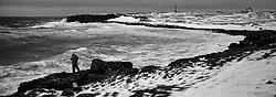 Man walking besides the coastline in stormy weather at the island Grimsey, north of Iceland - Maður á gangi við ströndina í Grímsey