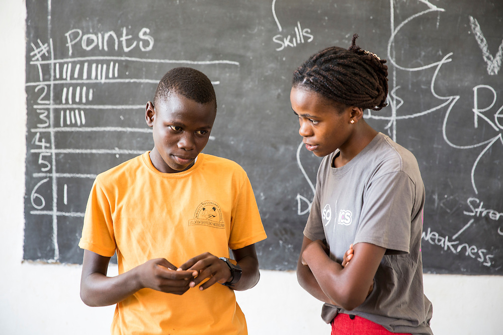 ICS volunteer Bertha Mhepela assisting a student with a mid class activity of positive English phrases charades at Mingoyo school as part of the VSO / ICS Elimu Fursa project (Opportunities in Education) Lindi, Lindi region. Tanzania.