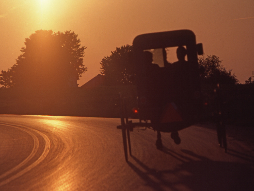 Amish buggy on road at sunset, Lancaster County