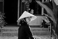 Young woman wearing a conical hat in ancient Hoi An.