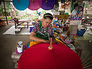 25 JUNE 2011 - CHIANG MAI, THAILAND: A woman makes an umbrella in a craft village near Chiang Mai, Thailand. Umbrellas from the Chiang Mai are prized throughout Thailand for the quality of workmanship. They were once used almost exclusively as sun parasols by Buddhist monks and royalty but now are used by hotels, restaurants and collectors.   PHOTO BY JACK KURTZ