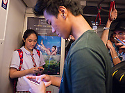 14 JULY 2011 - BANGKOK, THAILAND:  Thais check their smart phones while riding the Sukhmvit line of the BTS Skytrain in Bangkok. The Bangkok Mass Transit System, commonly known as the BTS Skytrain, is an elevated rapid transit system in Bangkok, Thailand. It is operated by Bangkok Mass Transit System Public Company Limited (BTSC) under a concession granted by the Bangkok Metropolitan Administration (BMA). The system consists of twenty-three stations along two lines: the Sukhumvit line running northwards and eastwards, terminating at Mo Chit and On Nut respectively, and the Silom line which plies Silom and Sathon Roads, the Central Business District of Bangkok, terminating at the National Stadium and Wongwian Yai. The lines interchange at Siam Station and have a combined route distance of 55 km.     PHOTO BY JACK KURTZ