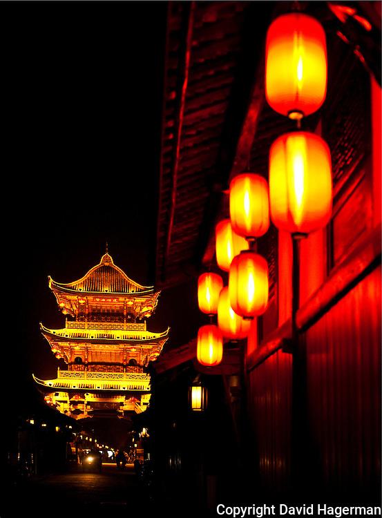 streets lined iwth red laterns and main pagoda of lang zhong ancient town at night