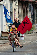 Two children riding on a bicycle are waving Albanian national flag as well as Democratic Party flag are gathered to support the pre-election campaign of Albania's democratic candidate for member of parliament of the democratic party Jozefina Topalli on Monday, June 22, 2009. (Photo by Vudi Xhymshiti)