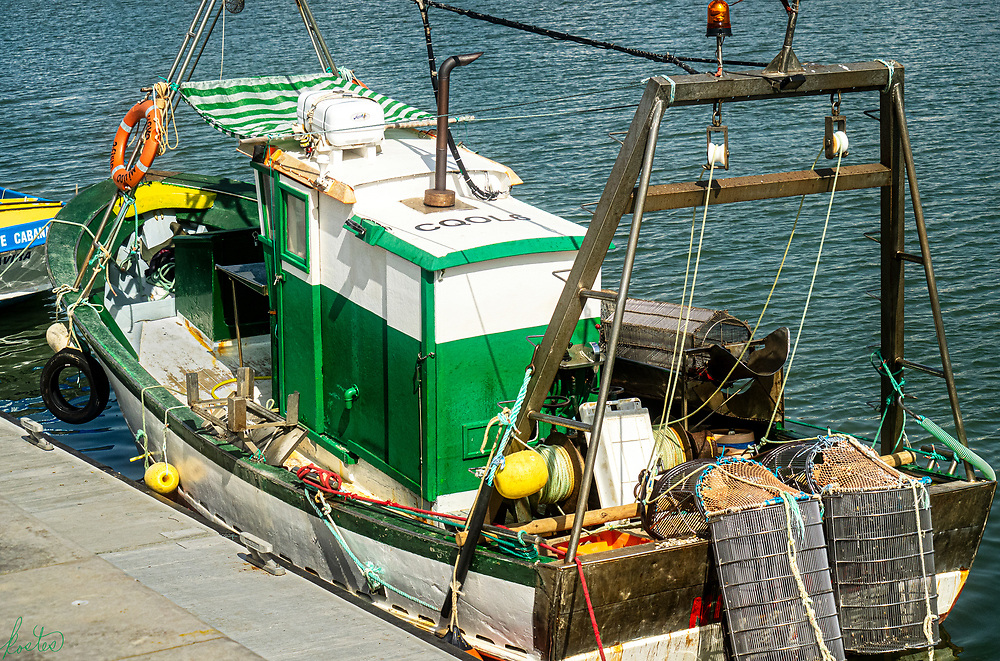 Crab Boat tied up along the dock of the Gilão river in Tavira, Portugal