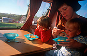 A mother feeds her small child alongside his older sister in a  1990s-era caravan while holidaying on a camping site in Cornwall, on 13th August 2000, in Looe, England. (Photo by Richard Baker / In Pictures via Getty Images)