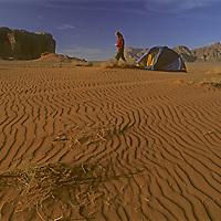 A woman camps in dunes below cliffs of Wadi Rum.