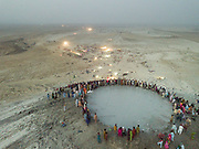"""As night approaches, the steep trek to the rim of the highest volcano is the first ritual of the Hinglaj pilgrimage. Pilgrims come up to throw a coconut in the cold mud (to thank the gods for granting their wish) and to apply the holy mud to their faces etc. The area around Chandragup (meaning """"Moon Well""""), a sacred site to Hindu of 3 mud volcanoes (mainland Asia's largest ones)."""