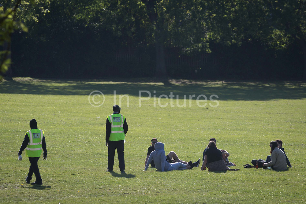 On the day that Coronavirus deaths passed the 20,000 mark in the UK, a Lambeth parks warden talks to a group of park users who are sitting on the grass, eventually moving them on to exercise and social distance elsewhere in Ruskin Park, a public green space in Lambeth, south London, on 25th April 2020, in London, England.