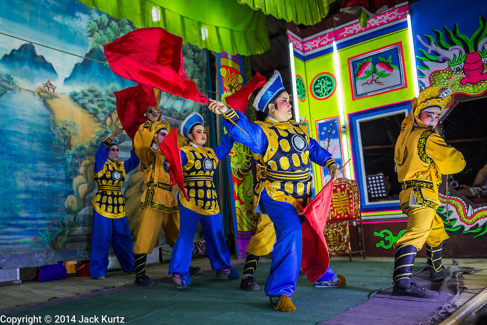 """25 JANUARY 2014 - BANG LUANG, NAKHON PATHOM, THAILAND: The Sing Tong Teochew opera troupe performs in a Chinese shrine in the village of Bang Luang, Nakhon Pathom, Thailand. The Sing Tong Teochew opera troupe has been together for 60 years and travels through central Thailand and Bangkok performing for mostly ethnic Chinese audiences.  Chinese opera was once very popular in Thailand, where it is called """"Ngiew."""" It is usually performed in the Teochew language. Millions of Chinese emigrated to Thailand (then Siam) in the 18th and 19th centuries and brought their cultural practices with them. Recently the popularity of ngiew has faded as people turn to performances of opera on DVD or movies. There are still as many 30 Chinese opera troupes left in Bangkok and its environs. They are especially busy during Chinese New Year when travel from Chinese temple to Chinese temple performing on stages they put up in streets near the temple, sometimes sleeping on hammocks they sling under their stage.     PHOTO BY JACK KURTZ"""