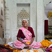 Hindu woman preparing flowers at temple in old town of Jaipur