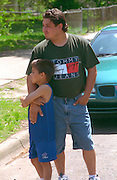 Mexican man age 25 and son age 9 watching Cinco de Mayo festival.  St Paul  Minnesota USA