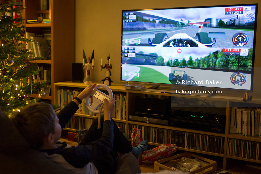A 10 year-old boy plays Formula 1 Wii on a widescreen TV on Christmas Day, on 25th December 2019, in Bristol, England.