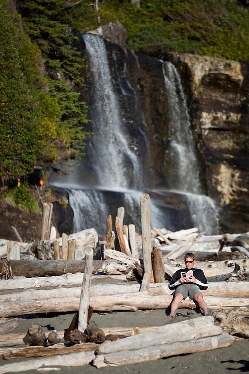 A man reads a book on the beach below Tsusiat Falls, West Coast Trail, British Columbia, Canada.