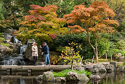 © Licensed to London News Pictures. 20/10/2020. LONDON, UK.  Visitors enjoy the autumnal display of changing leaves in the Japanese themed Kyoto Garden in Holland Park. The forecast is for a heavy rain to arrive in the next few days across much of the UK.  Photo credit: Stephen Chung/LNP