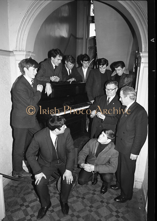 """Messrs. Pigott and Co. Ltd, handed over a piano to a group of students, calling themselves """"The Hooligans"""".  The students will push the piano to Cork, with the boys playing it on route and collecting on behalf of old age pensioners. Picture shows Mr. Michael Tobin, Pigott and Co., presenting the piano keys to Mr. W.J. Martin, who accepted them on behalf of the students who will push the piano; T. Conroy, D. Cullinane, S. Martin, M. Thunder, P. Frusco and Raymond Clancy..14.03.1964"""