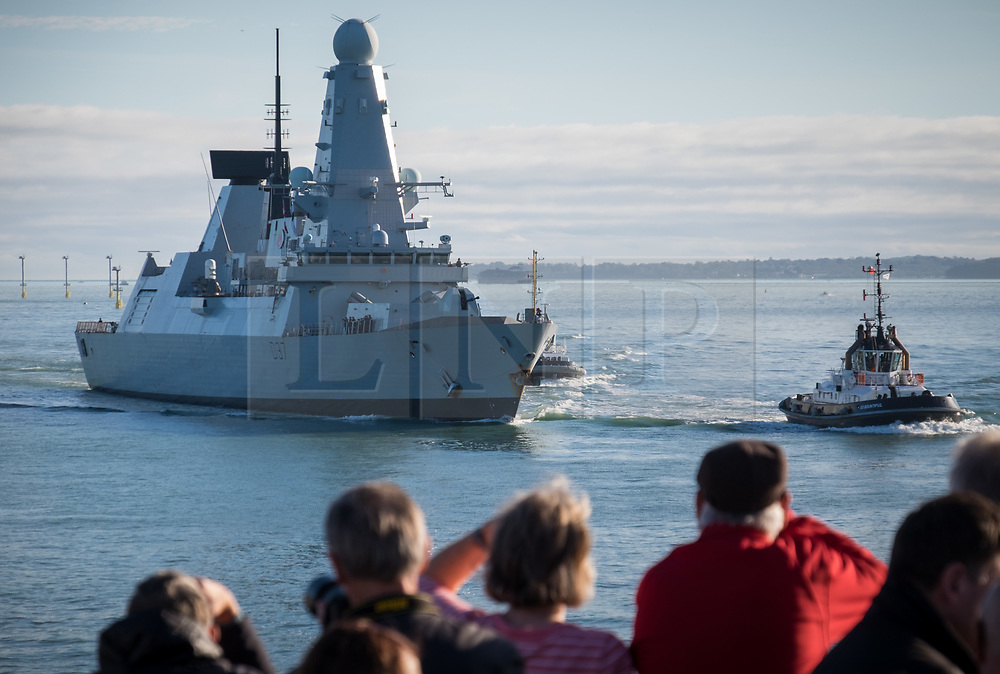 © Licensed to London News Pictures. 25/10/2017. Portsmouth, UK.  People watching as HMS Duncan (D37) approaches the entrance to Portsmouth Harbour today, 25th October 2017. The Type 45 destroyer has been in Portsmouth since September and is believed to be preparing to resume the role as flagship to the Standing NATO Maritime Group 2 (SNMG2) in the Mediterranean Sea, currently being fulfilled by HMS Diamond.  Photo credit: Rob Arnold/LNP