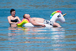 © Licensed to London News Pictures. 29/06/2018. Aberystwyth, UK. A man relaxes on a huge inflatable unicorn on the sea.  People flock to the seaside in Aberystwyth as the scorchingly hot  and very dry weather continues to dominate the UK. Photo credit: Keith Morris/LNP