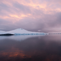 The sun sets over a small island near the Antarctic Peninsula, Antarctica.