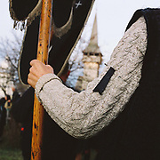 A man wearing a hand knitted woollen jumper holds a banner at a funeral, Botiza, Maramures, Romania