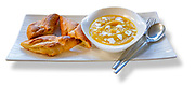 Placed on a long white plate a bowl of Pumpkin Soup with Sliced Baguettes and fork and spoon. RAW to Jpg