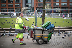 © Licensed to London News Pictures . 06/04/2017 . Manchester , UK . A street cleaner pushes his cart through pigeons in Manchester's Piccadilly Gardens . An epidemic of abuse of the drug spice by some of Manchester's homeless population , in plain sight , is causing users to experience psychosis and a zombie-like state and is daily being witnessed in the Piccadilly Gardens area of Manchester , drawing large resource from paramedic services in the city centre . Photo credit : Joel Goodman/LNP