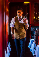 Waiter serving wine at lunch in the pillared pre-1940s dining car on the luxury Rovos Rail train between Pretoria and Cape Town, South Africa.