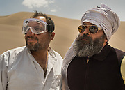 Two drivers with glasses to protect them from blasting sand.