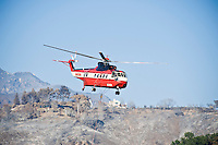 Water dropping fire fighting Helicopter with burnt landscape from Jesusita Fire, Santa Barbara, California, May 11, 2009