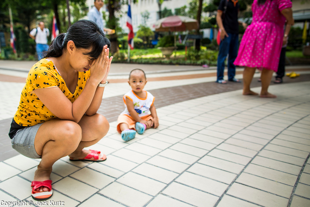 26 NOVEMBER 2012 - BANGKOK, THAILAND:  A woman, with her child nearby, prays for the hospitalized King in the courtyard at Siriraj Hospital, outside the wing housing the King of Thailand, in Bangkok. Siriraj was the first hospital in Thailand and was founded by King Chulalongkorn in 1888. It is named after the king's 18-month old son, Prince Siriraj Kakuttaphan, who had died from dysentery a year before the opening of the hospital. It's reported to one of the best hospitals in Thailand and has been home to Bhumibol Adulyadej, the King of Thailand, since 2009, when he was hospitalized to treat several ailments. Since his hospitalization tens of thousands of people have come to pay respects and offer get well wishes. The King's 85th birthday is on Dec 5 and crowds at the hospital are growing as his birthday approaches. The King is much revered throughout Thailand and is seen as unifying force in the politically fractured country.       PHOTO BY JACK KURTZ