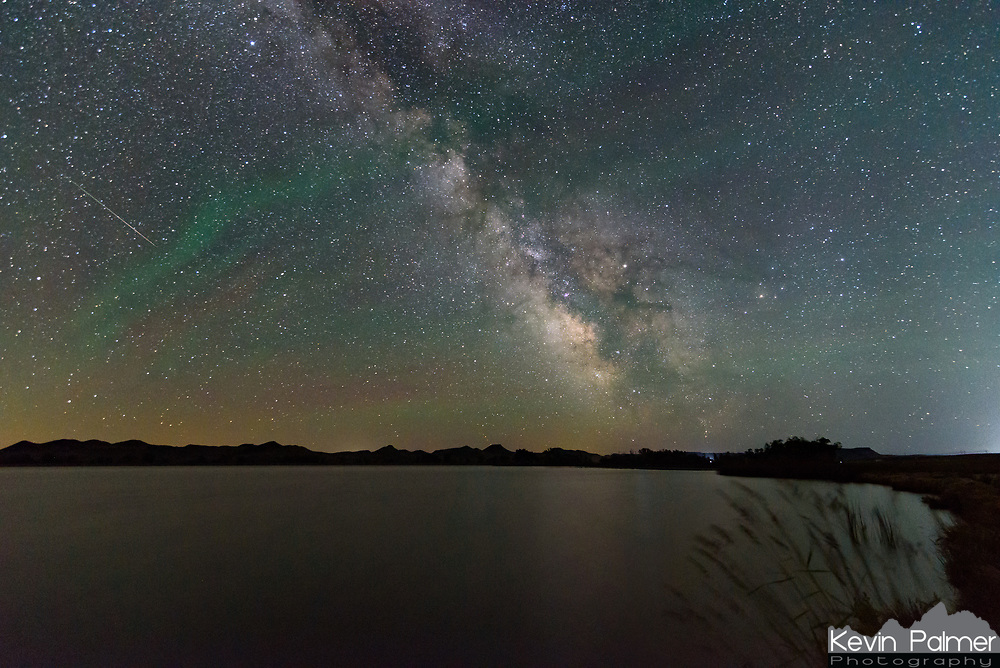 A sporadic meteor shoots through the sky while the milky way glows above Healy Reservoir.