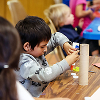 Lysanias Begay, 3, puts glue on bottle caps so his mom can put his name on his rocket at the Build Your Own Rocket event at the Children's Library on Wednesday afternoon in Gallup.