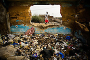 A girl walks past the ruins of a house filled with garbage in the Medina Gounass neighborhood of Guediawaye, Senegal on Thursday April 30, 2009.(Olivier Asselin for the New York Times)