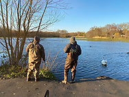 Wantagh, New York, U.S. April 22, 2020. Two fishermen wearing waders go to Mill Pond Park to fish as dusk approaches during Earth Day, on Long Island.