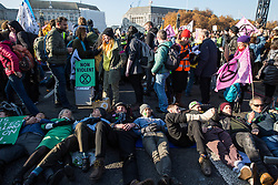 London, UK. 17th November, 2018. Environmental campaigners from Extinction Rebellion lie in the road to block Lambeth Bridge, one of five bridges blocked in central London, as part of a Rebellion Day event to highlight 'criminal inaction in the face of climate change catastrophe and ecological collapse' by the UK Government as part of a programme of civil disobedience during which scores of campaigners have been arrested.