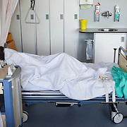 Nederland Rotterdam  31-08-2009 20090831 Foto: David Rozing .Serie over zorgsector, Ikazia Ziekenhuis Rotterdam. Vrouw op zaal ligt in ziekenhuisbed met haar hoofd onder de dekens. Woman patient in hospital bed, with her head under the blankets..Foto: David Rozing ..Holland, The Netherlands, dutch, Pays Bas, Europe, op zaal liggen,ziektekosten,zorgverlening, rust, rusten, uitrusten, bedrust, ziektebed, ongezond, slechte gezondheid, terugtrekken, op jezelf zijn,teruggetrokken, status,verbergen, verschuilen, wegkruipen, verstoppen, zwak, verzwakt, verzwakte toestand, niet zien zitten, ergens tegen iets op zien, het zwaar hebben, hiding, to hide, privacy, prive, afsluiten voor,ziektekosten,zorgverlening