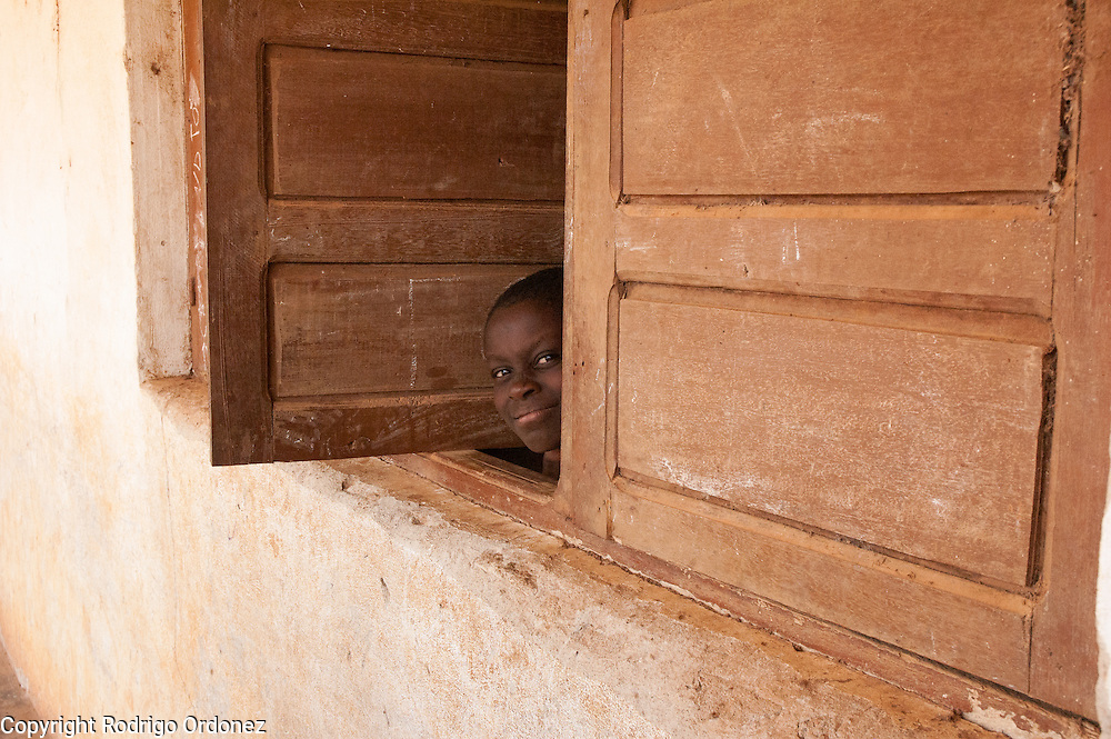 A girl peeks out of the window of a classroom.<br /> Save the Children distributed education kits to students at Groupe Scolaire Quartier Lycée in Man, western Côte d'Ivoire. Children received a backpack with school supplies such as pens, pencils, sharpeners, notebooks, rulers, a pair of compasses and a portable chalkboard.