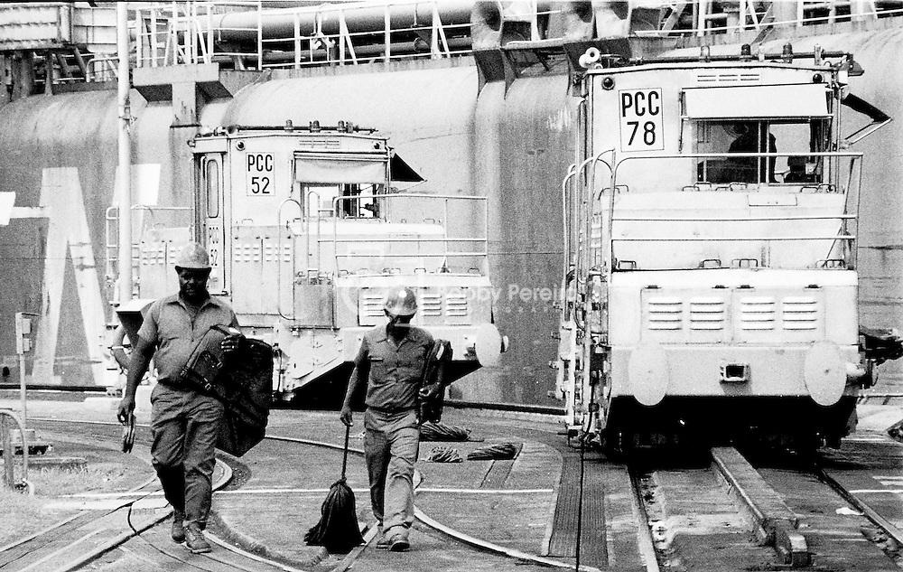 Panama Canal Employees walking next to the Miraflores Locks locomotives.