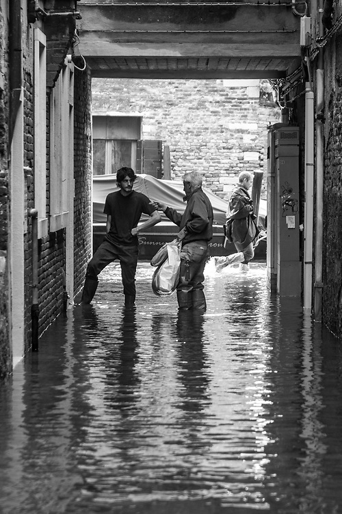 Venice, Italy. 29 October, 2018.  An old man speaks with a neighbour about the high tide that is entering into the house of him causing several damages in Cannaregio district on October 29, 2018, in Venice, Italy. This is a selection of pictures of different areas of Venice that the press has not covered, were resident live and every year they have to struggle with the high tide. Due to the exceptional level of the 'acqua alta' or 'High Tide' that reached 156 cm today, Venetian schools and hospitals were closed by the authorities, and citizens were advised against leaving their homes. This level of High Tide has been reached in 1979. © Simone Padovani / Awakening / Alamy Live News