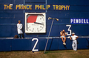 """Match officials at a Cartier polo tournament in Windsor Great Park, London. As time ticks on during the chukka, a scorer in a long white coat stands watching another as he checks his watch and listens to a transistor radio. We see that one team of the Prince Philip Trophy is Pendell Polo stables from Reading, England who have scored 3 points. Polo - from pulu in Hindi - referring to the wooden ball which was used, was adopted by the sport in its slow spread to the west. The first polo club was established in the town of Silchar in Assam, India, in 1834. It is also  called """"The Sport of Kings"""" and is a team sport played on horseback in which the objective is to score goals against an opposing team."""
