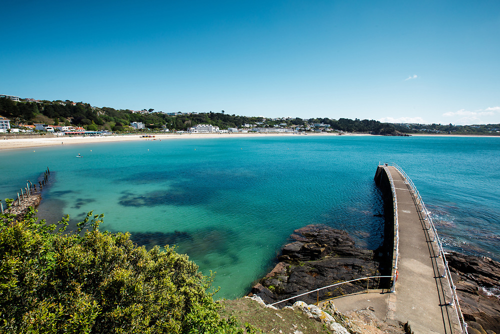 St Brelade's Bay, with its white sand, calm turquoise water and pier on a sunny summers day in Jersey, Channel Islands