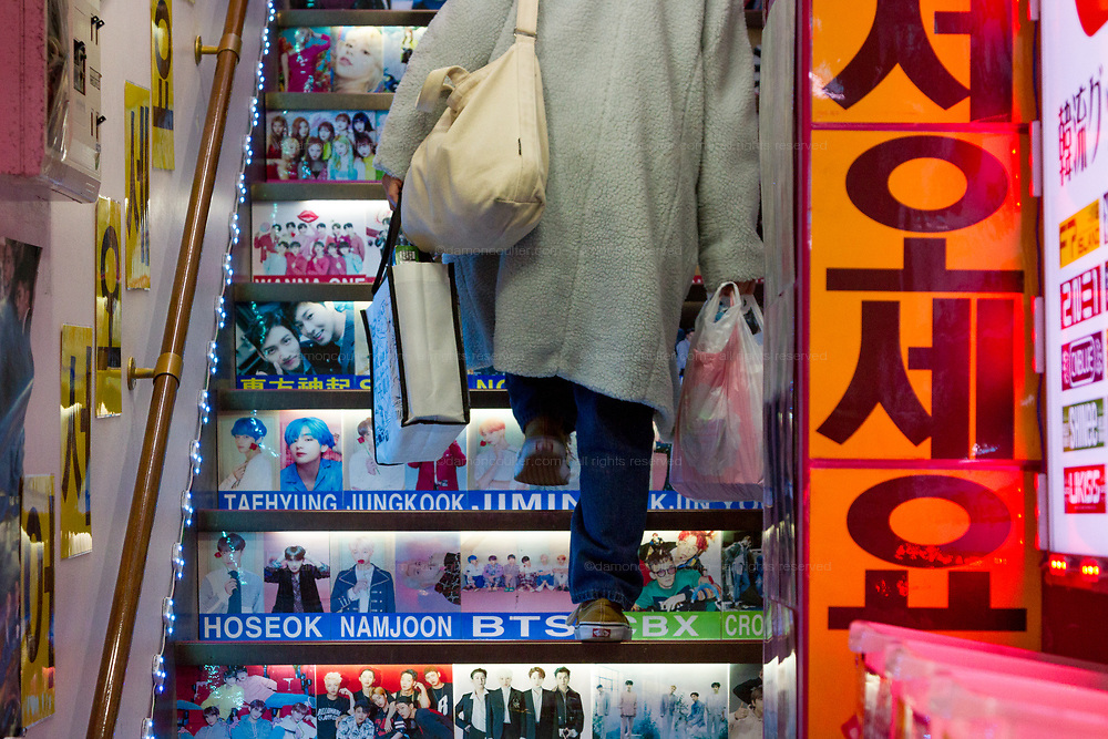 A woman carrying shopping bags climbs stairs with pictures of Korean idols and celebrities on them in a shop in Shin-Okubo, Shinjuku, Tokyo, Japan. Thursday December 19th 2019