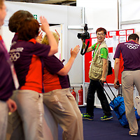 As a valedictory gesture, a photographer takes pictures of Olympic stewards within the badminton venue's media centre after the men's gold medal doubles match final during the 2012 London Summer Olympics.