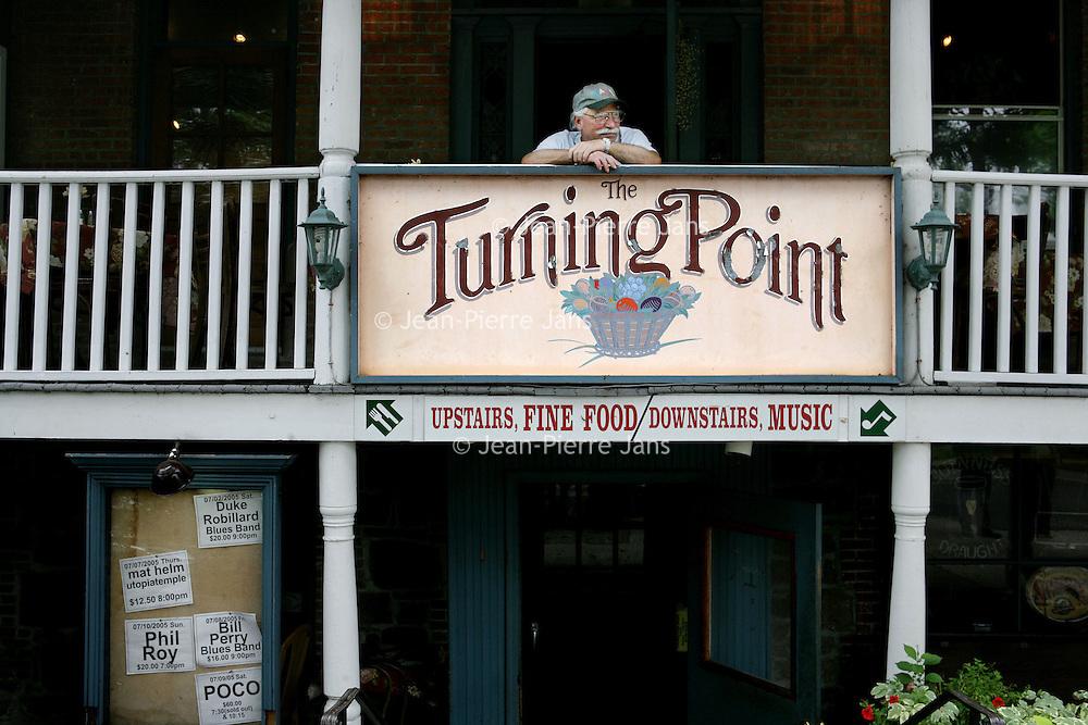 Verenigde Staten.Piermont.New York State.Rockland. 8 juli 2005.<br /> Straatbeeld in het centrum van Piermont, een dorpje aan de rivier de Hudson zo'n 30 km buiten New York city.<br /> Op de foto een buurtbewoner hangt over een balkon van een Jazz club annex kruidenierswinkel en kijkt naar winkelende mensen.Amerikaans.Lay back feeling.veranda.Fine food.<br /> Archives 2005, in the streets of Piermont, New York USA.
